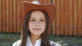 Portrait of the young girl puts on hat and smiling at camera. Slowly - 175404956
