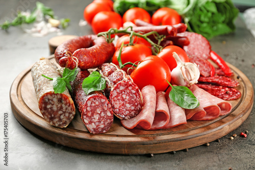 Delicious sliced sausages with vegetables on wooden board