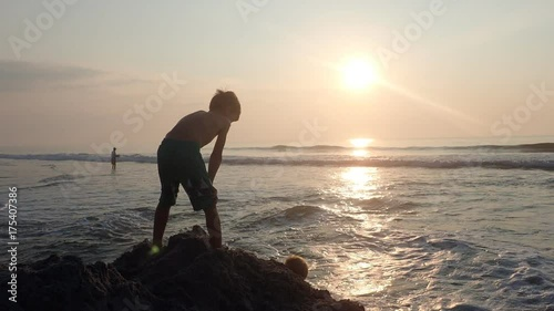Little boy playing on beach at sunrise