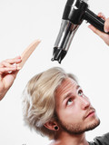 Young man drying hair with hairdryer - 175431513