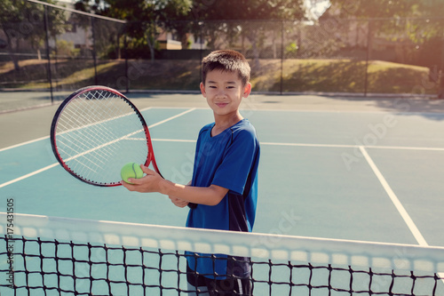 Fotobehang Tennis Young tween Asian boy tennis player on outdoor blue court