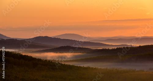 Fotobehang Zonsopgang Beautiful landscape at sunrise with foggy hills
