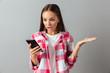 Portrait of a shocked pretty woman in plaid shirt