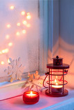 Red Christmas lantern and candle in dusk on old windowsill. - 175435764