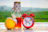 Fresh organic honey in glass jar , measuring tape , lemon and alarm clock on old wooden with blurred background ,healthy nutrition,strengthening immunity, diet and treatment of flu - 175436795