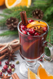 Traditional hot winter mulled wine with citrus, cranberry, cinnamon, cardamom and star anise in a glass on the table. Christmas. New year. Selective focus - 175438795
