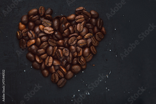 Papiers peints Café en grains Coffee in beans on dark background. Coffee beans in the form of heart. Abstract background texture.Coffee beans texture. Food background of coffee beans