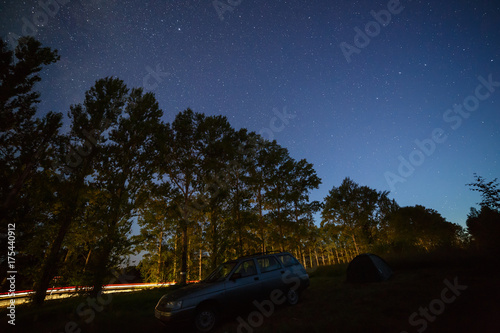 Staande foto Nacht snelweg Stars in the night sky over the highway in the forest.