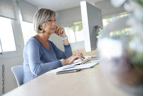 Senior woman working in office on desktop computer - 175442151
