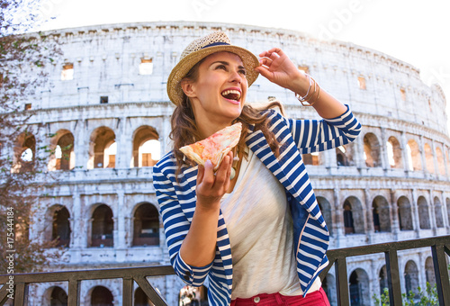 tourist woman with pizza slice looking into the distance