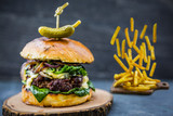 Tasty grilled beef burger with spinach lettuce and blue cheese served on wooden table with copyspace, blackboard in background. - 175452330