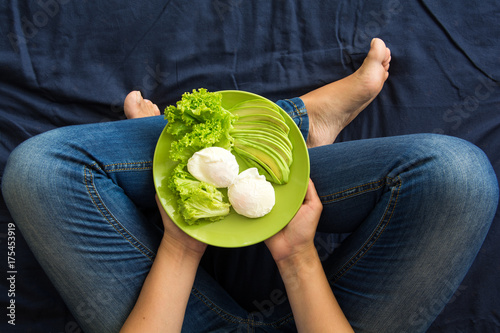 Foto Murales Healthy eating concept. Women's hands holding plate with lettuce, avocado slices and poached eggs. Top view