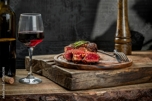 Foto op Aluminium Steakhouse Grilled ribeye beef steak with red wine, herbs and spices on wooden table