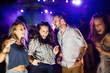 Group of friends having fun and dancing at concert