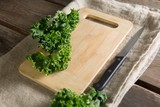 Kale on cutting board with knife at table - 175467307