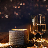 Bright radiant gift box with champagne and bokeh background