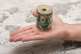 A man holds a bundle of money in his hand tied with an elastic band - 175467770