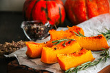 Roasted pumpkin slices with rosemary and dry thyme on a baking paper on a wooden background. - 175471349