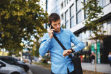 Businessman talking on the phone and looking at his watch in the city - 175477549