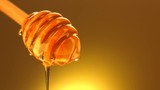 Honey dripping from honey dipper isolated on yellow background. 4K UHD video footage. Ultra high definition 3840X2160 - 175485329