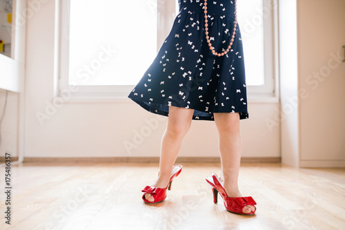 Unrecognizable little girl in dress and red high heels at home. - 175486357