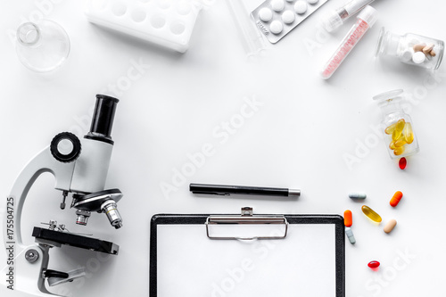 Doctor's workplace. Microscope, tablet, pills and test tube on white background top view copyspace