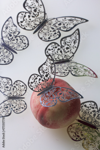 A ripe juicy peach lies on a white surface. All around is decorated with butterflies cut from foil. - 175507788