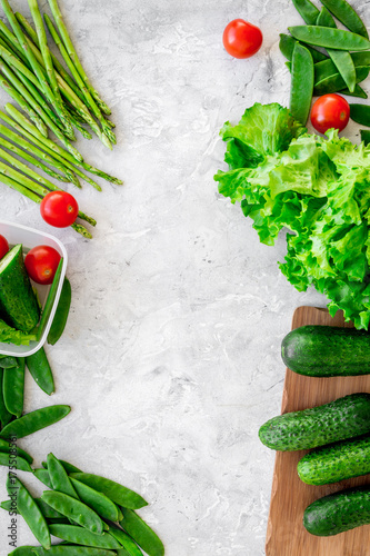 Healthy meal with vegetables tomato, cucumber, asparagus, salad, pea on grey background top view copyspace