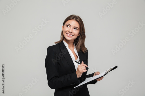 Portrait of a smiling young businesswoman in suit - 175510333