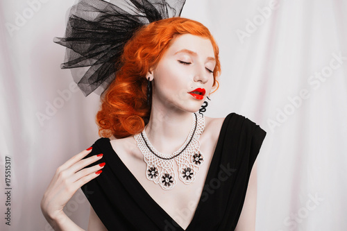 Plakát Redhead woman with unusual appearance in black dress and veil on the head and red lips