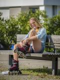 Frau, 22 Jahre, beim Inline Skaten, sitzt auf Parkbank, zieht Skates an, Wohngebiet