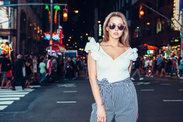 Beautiful woman wearing stylish fashionable outfit posing on night city street in New York