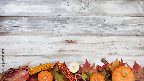 Bottom border of Autumn foliage with other fall decorations on white rustic wooden boards - 175539779
