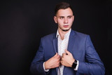 Successful young businessman in business suit and white shirt and fashionable clock on hand on a black background. Stylish man. Men's professions - 175547781