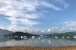 Mountain, blue sky, recreational boats and cloudscape with reflection on lake