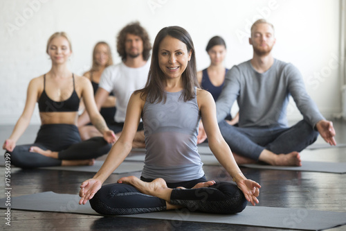 Group of young sporty people practicing yoga lesson with instructor, sitting in Poster