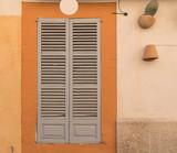 Fensterladen in einer Fassade vor einem Fenster - 175560902