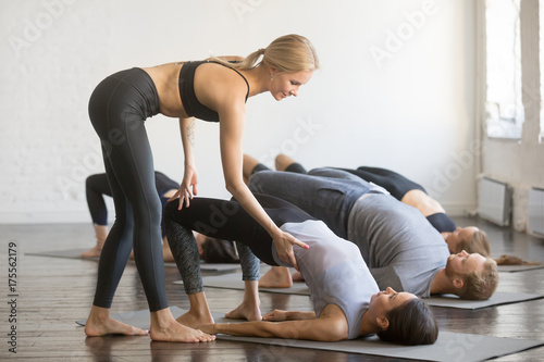 Wall mural Group of young sporty people practicing yoga lesson with instructor, stretching, doing Glute Bridge exercise, female teacher correcting dvi pada pithasana pose, working out, indoor full length, studio