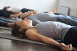 Leinwanddruck Bild - Group of young sporty people practicing yoga lesson with instructor in gym, lying in Dead Body exercise, doing Savasana, Corpse pose, friends relaxing after working out in sport club, studio image