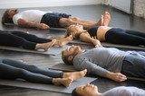 Group of young sporty people practicing yoga lesson with instructor in gym, lying in Dead Body exercise, doing Savasana, Corpse pose, friends relaxing after working out in sport club, indoor image - 175562333