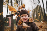 Little laughing girl in front of her throwing autumn leaves in the park. On the back of the blurry terms of the older girl. Muted soft colors. - 175563118