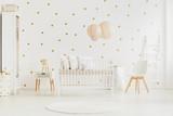 Pastel lanterns above baby's bed - 175565123