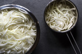 Sliced onions with straws in a bowl and in a saucepan for onion soup - 175568395