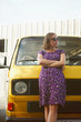 Young content woman in dress and sunglasses dreaming while posing near yellow van on nature.