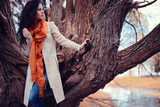 young girl in an orange scarf on a walk in the park - 175577948