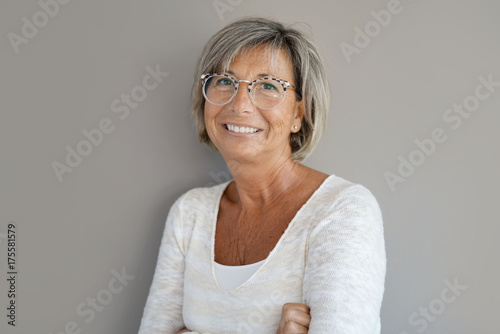 Papiers peints Echelle de hauteur Portrait of mature woman with eyeglasses on grey background