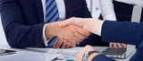 Business handshake at meeting or negotiation in the office, close-up. Partners are satisfied because signing contract or financial papers