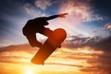 Skateboarder jumping at sunset. - 175593720