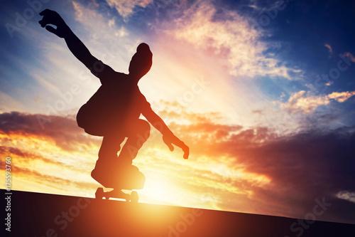 Fotobehang Skateboard Man skateboarding at sunset.