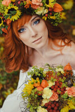 autumn portrait of romantic redhead woman with flowers in her hair in a wreath